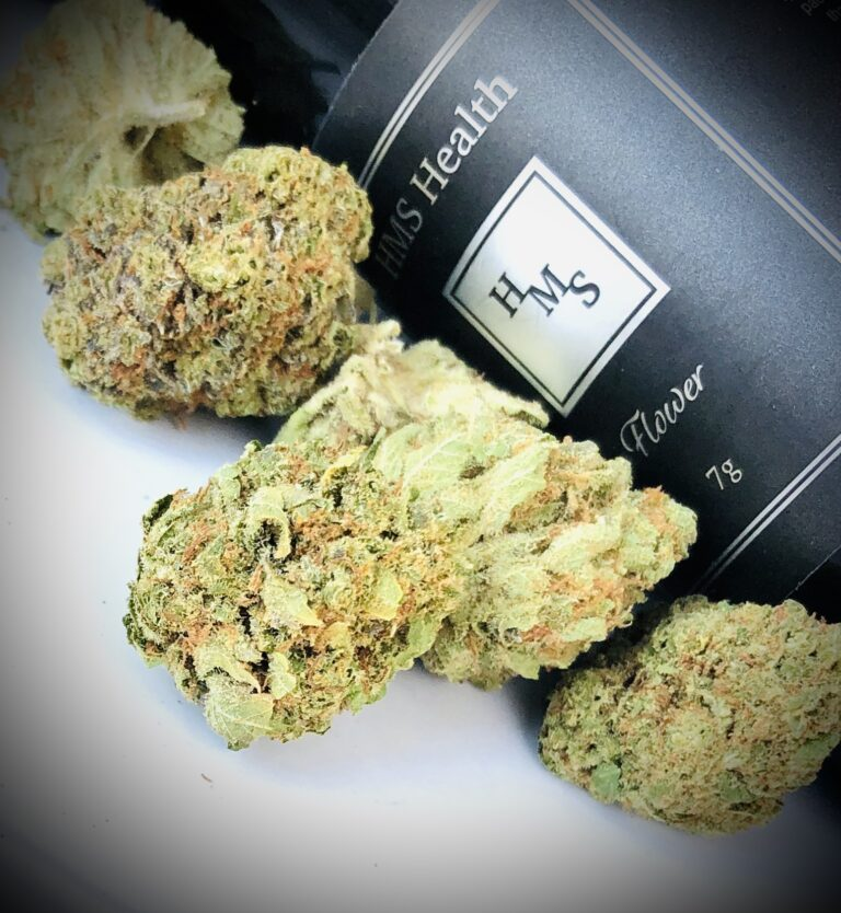 slanted photo of hms pineapple kush buds in front of hms black and silver quarter ounce container