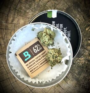 grow west tin from above with lid off and underneath on wood surface with boveda terpene pack and two buds of triangle kush by grow west