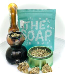 sherlock pipe and the soap strain with culta ziplock in background and grinder filled with shake in foreground