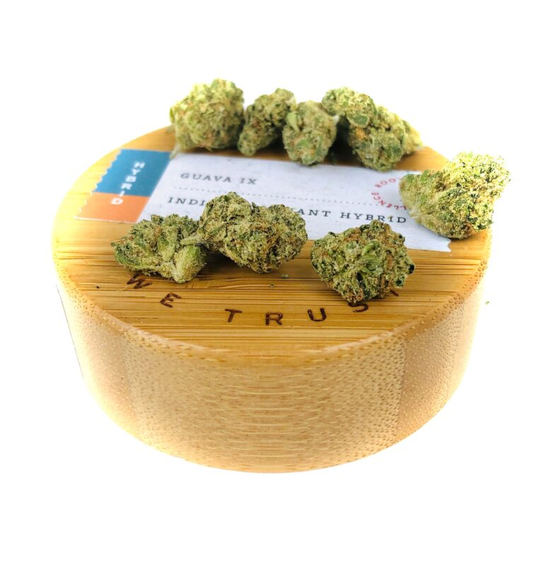 wooden lid of natures heritage 7 gram jar with buds of guava ix strain on top