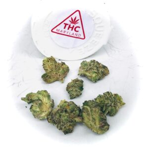buds of cookie face in the shape of a smiley face with thc sticker in red behind