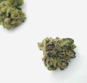white trichomes on a green yellow and brown bud of gummiez by strane
